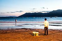 Homem na orla da Praia do Pântano do Sul ao anoitecer. Florianópolis, Santa Catarina, Brasil. / Man standing by the shore at Pantano do Sul Beach at evening. Florianopolis, Santa Catarina, Brazil.