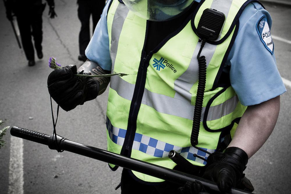 Riot officer holds flower, Plan Nord demonstration, Quebec Spring / Printemps Érable.