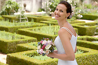 Mid adult bride in garden holding bouquet smiling