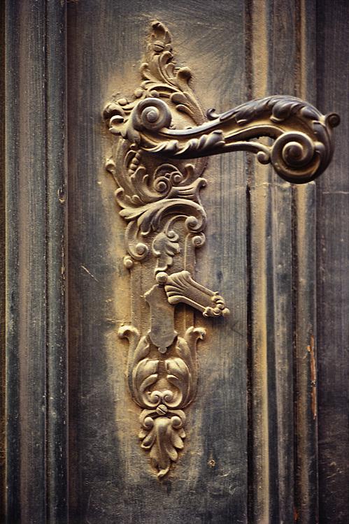 Ornate European doorknob in a old wooden door Damian Hevia