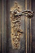 Ornate European doorknob in a old wooden door.