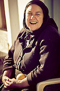 This yiayia (grandmother), is enjoying the warm Sunday  sun, in the village of Krousta Crete, Greece.