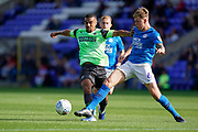 Kwesi Appiah of AFC Wimbledon tackles Frankie Kent of Peterborough United during the EFL Sky Bet League 1 match between Peterborough United and AFC Wimbledon at London Road, Peterborough, England on 28 September 2019.