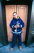 DJ Adam F standing in a doorway holding a trumpet