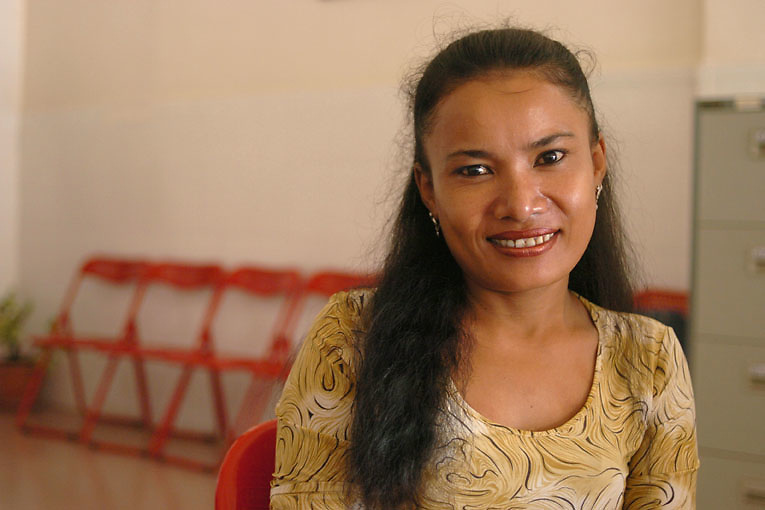 Cambodia. Phnom Penh. 2006. An outreach worker in the Chhouk Sar centre reacts to the camera with a smile. Chouk Sar, is a drop in centre for sex workers living with HIV, they also provide home based care through their five outreach workers, who are all living with HIV and have formerly worked as sex workers themselves.