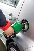 A hand of a man filling up unleaded petrol at a petrol station