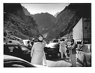 Passenger scans canyon walls during traffic jam in Taliban ambush country.  Traffic snarled because of an Italian military checkpoint (one soldier seen standing on the road ahead) at the bottom of massive canyon through which passes the Kabul - Jalalabad Road, Afghanistan.