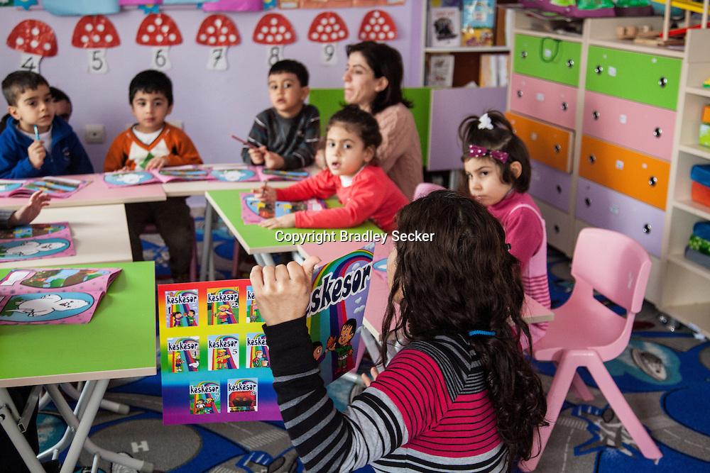 DIYARBAKIR, TURKEY. FEBRUARY 22, 2013 Teacher Valide, bottom, begins her class for young Kurdish children in Diyarbakir. The creche only teaches in Kurdish, something which was banned until recently in Turkey.