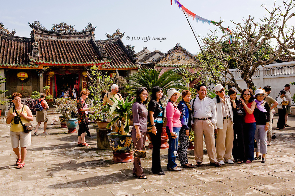 Asian and European tourists in front of a pagoda in Vietnam;.   The Asians are grouped for a photograph while the Europeans wander individually around the area.  An example of comparative social behavior of Orientals and Caucasians.