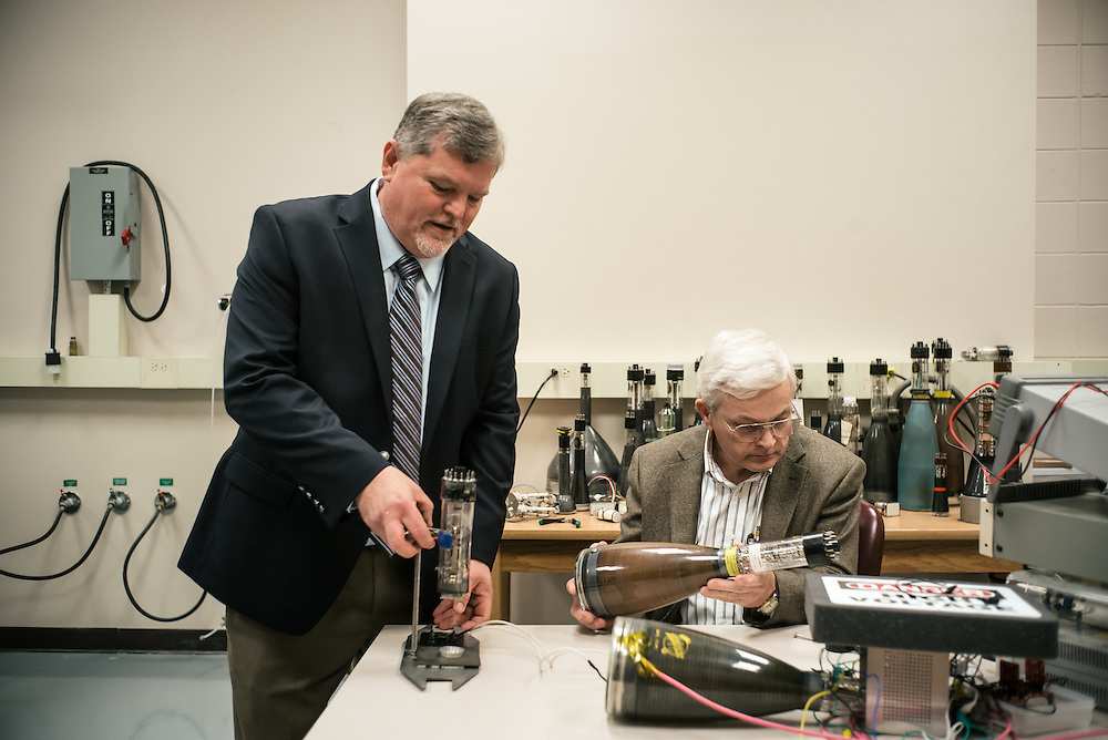 """AUBURN, AL – NOVEMBER 20, 2016: Bart Prorok (left) and Tony Overfelt (right) examine antique cathode ray tubes from television sets for use in an additive manufacturing experiment. In 2016, Auburn University received a grant to develop low cost additive manufacturing techniques, which would allow small businesses interested in additive manufacturing to cheaply test the method's viability for their unique production needs. By repurposing the infrastructure inside cathode ray tubes, the existing electron gun inside the tubes is harnessed for additive manufacturing. """"All the infrastructure used in the million dollar machines is right here in these tubes,"""" Prorok said. """"It's more crude, and tuned to a different application, but it's there. We're trying to harness them to do something new."""" Prorok believes the method has potential to become the new paradigm for how newer additive manufacturing machines are built.<br /> <br /> In much of the United States, global trade and technological innovation has failed to produce the prosperity hoped for by political and business leaders. Yet despite formidable economic challenges, some localities are flourishing. In Lee County, Ala., unemployment is below the national average despite the loss of thousands of manufacturing jobs, and the key to the county's resilience may be Auburn University, which provided a steady source of employment during recessions and helped draw new businesses to replace those that fled. CREDIT: Bob Miller for The Wall Street Journal<br /> [RESILIENT]"""