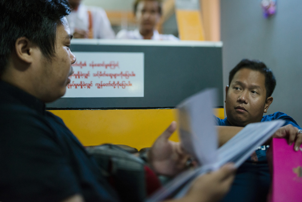 Yangon 20160917<br /> Thar Ko and Ye Htut Soe at a massage salon &quot;for men&quot;. Thar Ko is flipping through a look book with the different masseurs.<br /> Photo: Vilhelm Stokstad / Kontinent