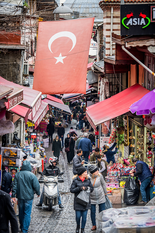 The Turkish flag hangs in between buildings in narrow street with shop selling goods below, Istanbul, Turkey