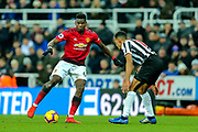 Paul Pogba (#6) of Manchester United takes on Isaac Hayden (#14) of Newcastle United during the Premier League match between Newcastle United and Manchester United at St. James's Park, Newcastle, England on 2 January 2019.