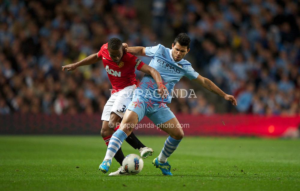 MANCHESTER, ENGLAND - Monday, April 30, 2012: Manchester City's Sergio Aguero in action against Manchester United's Patrice Evra during the Premiership match at the City of Manchester Stadium. (Pic by Chris Brunskill/Propaganda)