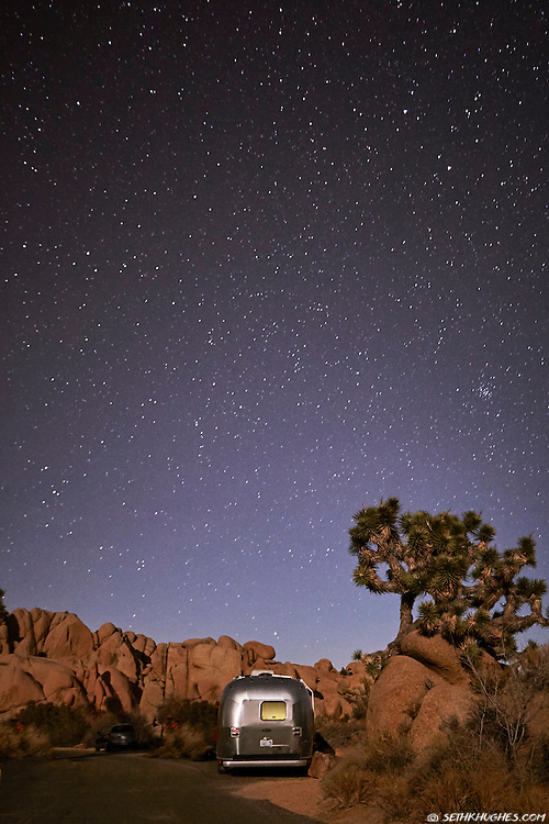An Airstream RV trailer is camped below a sky full of stars in Joshua Tree National Park, California.