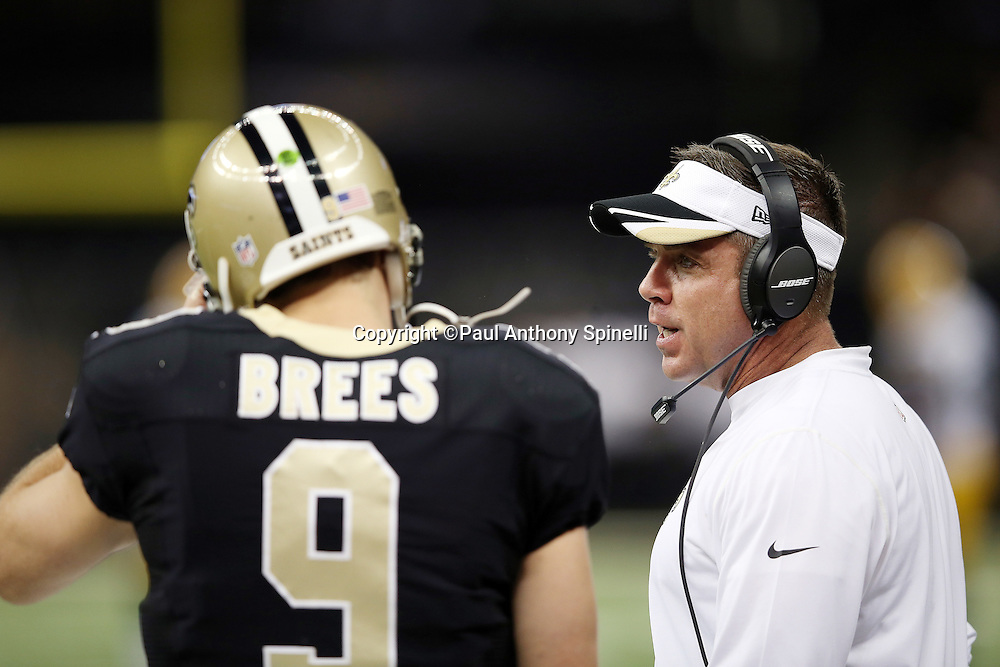 New Orleans Saints quarterback Drew Brees (9) meets with New Orleans Saints head coach Sean Payton on the sideline during the NFL week 8 regular season football game against the Green Bay Packers on Sunday, Oct. 26, 2014 in New Orleans. The Saints won the game 44-23. ©Paul Anthony Spinelli