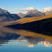 calm lake mcdonald, reflecting the brilliant colors of fall larch, glacier national park