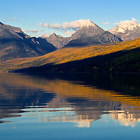 calm lake mcdonald, reflecting the brilliant colors of fall larch, glacier national park