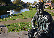 "Bronze casting of writer Brendan Behan, on the Royal Canal, Dublin, by sculptore John Coll. The bench and statue are near Mountjoy Prison, where Behan spent time; his play, the Quare Fellow, features a song called ""The Auld Triangle"" which mentions the Royal Canal. The casting features triangles..."