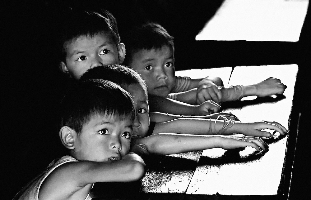 Four to a desk for these attentive students in Kantabua Village, Savannakhet province, Laos.