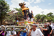Apr. 25 -- UBUD, BALI, INDONESIA:  Members of the family carry the bull that will Cokorde Gede Raka will be cremated in at the funeral for Gede Raka, a member of Ubud's royal family Sunday, Apr. 25. Balinese are Hindus and cremate their dead. Balinese funerals are elaborate - and expensive - affairs. A funeral for one person costs a minimum of 45 million rupiah (about $5,000 US). The body is placed into the bull's body at the cremation and cremated in the bull. The funeral pyre is burnt adjacent to the bull. That is what a family may earn in two to three years. The result is that only the rich can afford formal cremations. The body (in the casket) is placed in the top of the funeral pyre and the procession takes the body to the cremation site. The funeral pyre, and the body, are spun at intersections to confuse the spirits so the soul doesn't try to return to its home and to confuse evil spirits.    PHOTO BY JACK KURTZ
