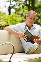 Man sitting on sofa in back yard reading book