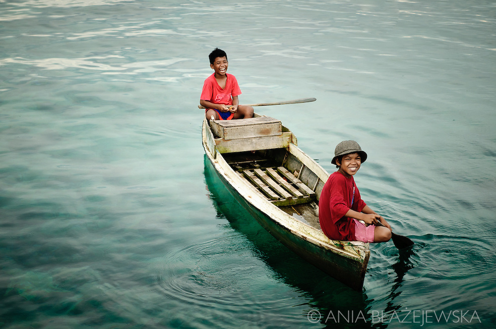 Philippines, Tawi Tawi. Boys from Simunul Island coming back home by boat.