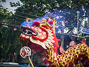 30 OCTOBER 2014 - BANGKOK, THAILAND: Chinese style dragon dancers perform on Chakkaphatdi Phong Street during the parade marking the start of the annual temple fair at Wat Saket. Wat Saket is on a man-made hill in the historic section of Bangkok. The temple has golden spire that is 260 feet high which was the highest point in Bangkok for more than 100 years. The temple construction began in the 1800s in the reign of King Rama III and was completed in the reign of King Rama IV. The annual temple fair is held on the 12th lunar month, for nine days around the November full moon. During the fair a red cloth (reminiscent of a monk's robe) is placed around the Golden Mount while the temple grounds hosts Thai traditional theatre, food stalls and traditional shows.   PHOTO BY JACK KURTZ