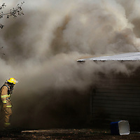 Thomas Wells | BUY at PHOTOS.DJOURNAL.COM<br /> A lone Shannon fire fighter heads back into a house fire on Lee County 857 in the Brewer Community Tuesday. There were no injuries and the house was a complete loss.