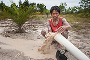 Santo (30 ans), a tin miner, digs in his own garden to find tin sand, he gets until 3 kilos a day. This illegal tin mine is the only source of income for his family in Mapur, Bangka Island, Indonesia. The demand for tin has increased due to its use in smart phones and tablets. Illegal tin mining causes environmental damage, injuries and regular casualties (100-150 persons die every year) among miners.   <br /> <br /> Santo (30 ans), un mineur d'étain, creuse dans son jardin pour trouver de l'étain, il trouve jusqu'à 3 kilos par jour. Cette mine d'étain illégale est la seule source de revenus pour sa famille dans Mapur, île de Bangka (Indonésie).  La demande de l'étain a explosé à cause de son utilisation dans les smartphones et tablettes. Les Mines illégales son la cause des dommages écologiques, des blessés graves et décès (100 - 150 tous les ans) chez les mineurs.