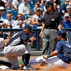 March 21, 2012; Port Charlotte, FL, USA; Tampa Bay Rays first baseman Carlos Pena (23) slides safely past New York Yankees third baseman Alex Rodriguez (13) during the bottom of the fourth inning of a spring training game at Charlotte Sports Park.  Mandatory Credit: Derick E. Hingle-US PRESSWIRE