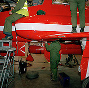 Engineering specialists perform routine maintenance in the Red Arrows team hangar. Dressed in their green overalls, members of the Red Arrows 'Blues' the back-up team, (so-called after their distinctive blue overalls worn only during the summer) perform routine engineering tasks in the hangar at RAF Scampton, Lincolnshire. The better-educated officers in the armed forces enjoy a more privileged lifestyle than their support staff. In the aerobatic squadron, the Blues outnumber the pilots 8:1. Without them, the Red Arrows couldn't fly. Some of the team's Hawks are 25 years old and their air frames require constant attention, with increasingly frequent major overhauls due..