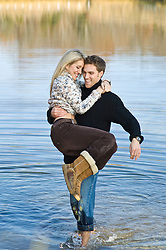 Man carrying a girl in a pond