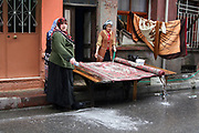 Turkish women cleaning a carpet in a street in Istanbul, Turkey