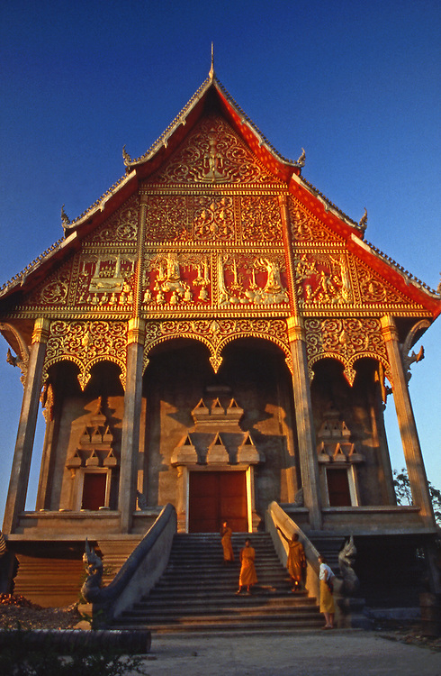 Buddhist temple in red and gold in Luang Prabang, Laos with monks and visitor