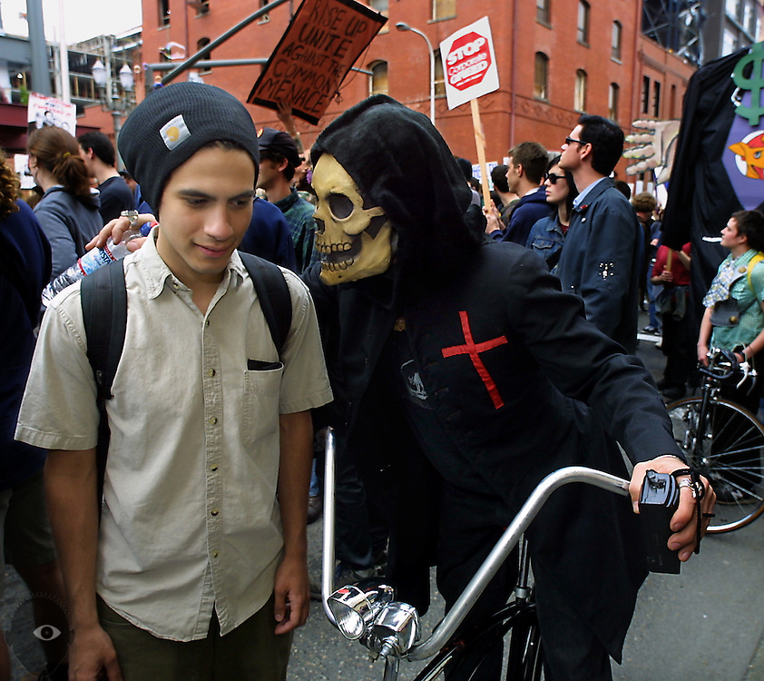 Participants interact during a May Day parade through downtown Portland, some wearing strange costumes and pushing their own agendas.