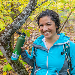 A woman takes a break during a hike in the Raymond Community Forest in Raymond, Maine. Fall.