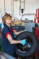 Portrait of a confident young female mechanic carrying tire in vehicle repair shop