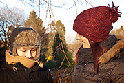 Mother wearing red hat and black jacket smiles at her 12 year old son who is wearing a mustard coloured scarf. There are trees in the background and hazy blue sky, Moffat, Annandale Way.
