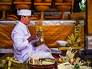 "08 AUGUST 2017 - UBUD, BALI, INDONESIA: A Hindu priest leads a service during a ceremony to honor a family temple in Ubud, Bali. Balinese Hindus have a 210 day calender and every almost every family compound on Bali has a family temple. Once a year (or every 210 days) families celebrate the ""birthday"" of their temple with a ceremony.     PHOTO BY JACK KURTZ"
