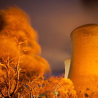 Australia, Victoria, Yallourn, Time exposure of Tru Energy coal-fired power station and surrounding trees being blown in strong winds at night