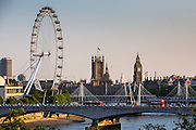 A view of the Houses of Parliament including Big Ben taken from the North Bank of the River Thames, London, United Kingdom. The London Eye wheel is located on the south bank. Traffic drives past on Waterloo bridge including a double decker red bus.