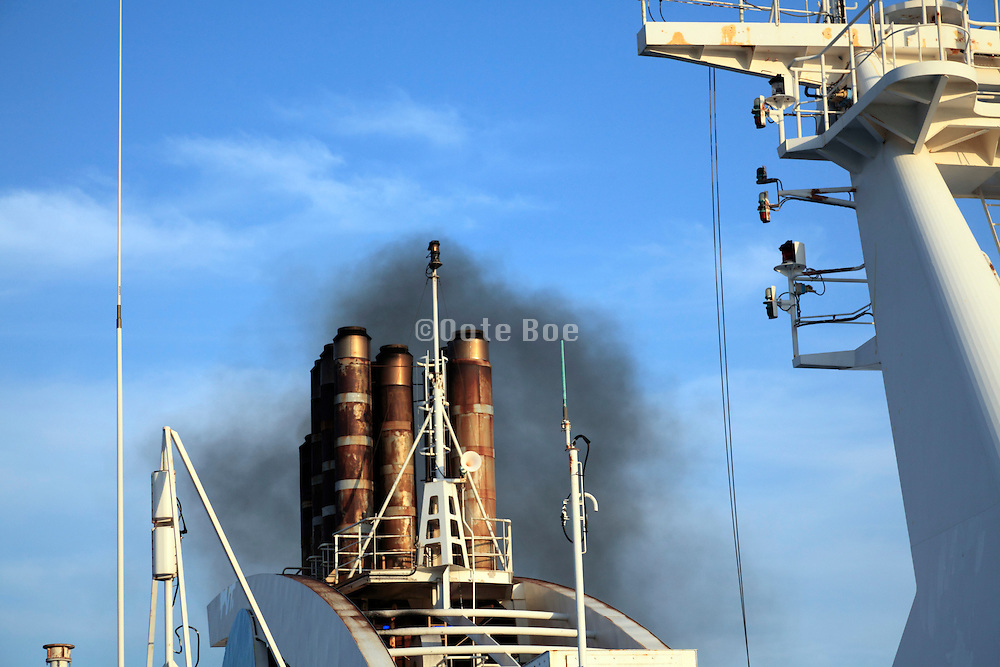 black smoke bellying from the smokestacks of a large ferry ship