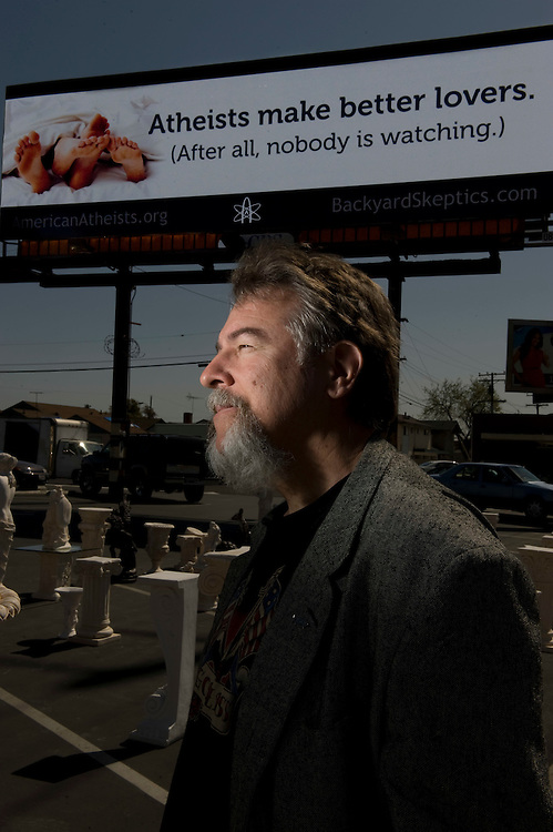 "Bruce Gleason, the ""most outted atheist"" in Orange County, and leader of Back Yard Skeptics, poses with the Valentine's day billboard the group put up along Beach Blvd in Midway City."