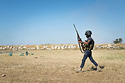 An Iraqi federal police officer carries a sniper rifle during a sniper training course carried out by Iraqi federal police and the US Army near Mosul on May 16, 2017.