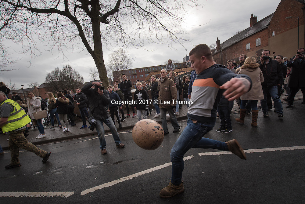 "Atherstone, Warwickshire, UK. 28th February 2017. Pictured:  Participants kick the ball in the centre of Atherstone. / Hundreds of people of all ages flood into the Warwickshire town of Atherstone to either participate or watch the infamous Atherstone Ball Game. The event is being held for the 818th time opening when this year's celebrity, Eastenders star Annette Badland, throws the ball into the crowd of people. The Atherstone Ball Game is an ancient Shrove Tuesday tradition in which the people of this rural North Warwickshire town awaken and literally brawl over a large ball up and down the town's small ancient streets. Shops are boarded up, local schools are closed and towns people of Atherstone gather in the main street at 3pm with only one rule in mind, the ball cannot be taken outside the town. Anything and everything else goes. The winner in this no holds barred contest is the person holding onto the ball at 5pm. This traditional Shrove Tuesday Ball Game has been held annually since the early 12th Century and is one of Atherstone's claims to fame. The origin of the game, in the reign of King John, is thought to have been a ""Match of Gold that was played between the Warwickshire Lads and the Leicestershire Lads on Shrove Tuesday"".  // Lee Thomas, Tel. 07784142973. Email: leepthomas@gmail.com  www.leept.co.uk (0000635435)"