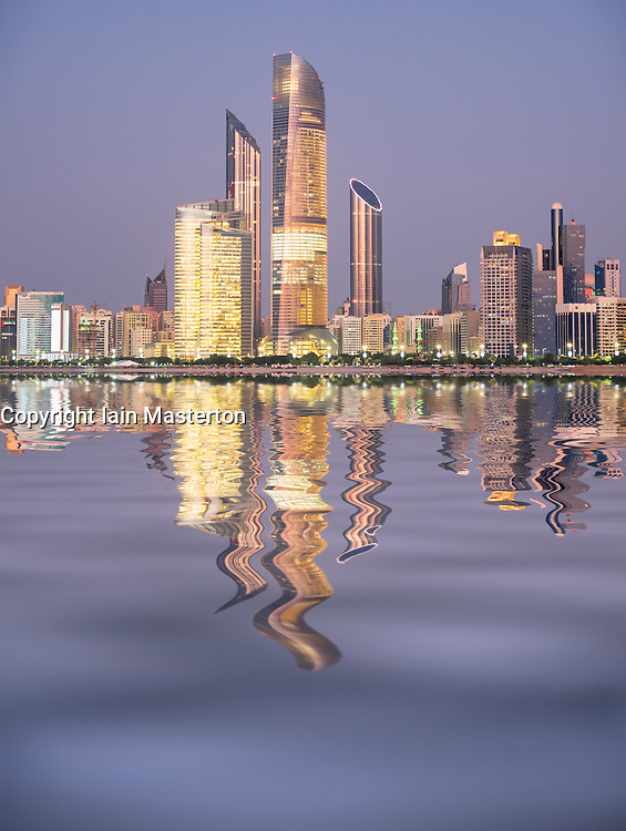 Skyline and reflection of modern buildings along Corniche waterfront in Abu Dhabi United Arab Emirates