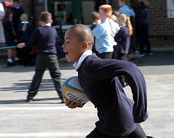 Boy running with rugby ball during playtime in primary school; West Yorkshire UK
