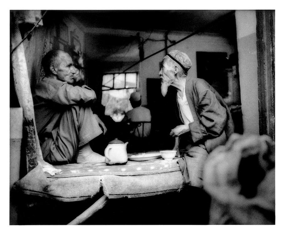 Uighur men talking over tea near Id Kah Mosque, Kashgar, Chinese Turkestan. 2002
