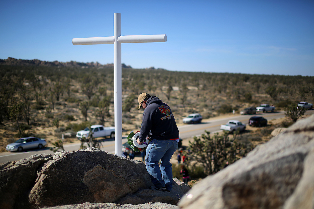 A military Veteran lays a wreath at a cross during an unveiling ceremony for the Mojave Cross on Veterans Day in Cima, California on Sunday, November 11, 2012.  A battle has been brewing for over Thirteen years over whether the cross can legally stay on Sunrise Rock because it violates Separation of Church and State and is in the Mojave National Perserve which is on Federal Lands.  The Veterans of Foreign Wars and American Legion Society raised money to purchase the plot of land and has kept the cross in place and today serves as war memorial.(Photo by Sandy Huffaker)